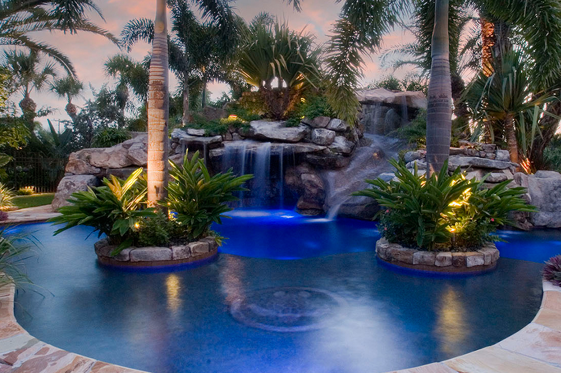 Custom pool with raised rock walls, water fountains, and much more