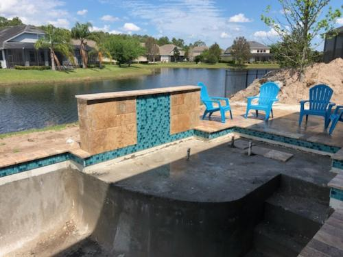 St-Agustine-pool-construction-travertine-deck-raised-wall-waterfall-1