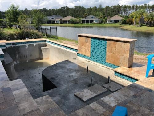 St-Agustine-pool-construction-travertine-deck-raised-wall-waterfall-2